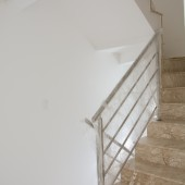 Escada toda em marmore travertino e corrimaõ em aço inox escovado